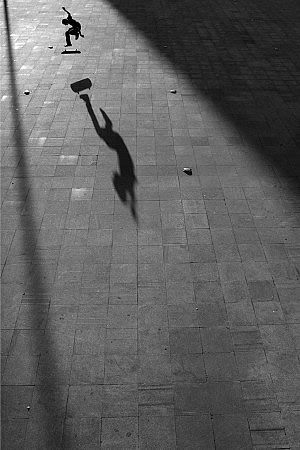 skateboarder jumping with shadow
